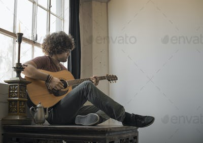 Loft living. A young man playing guitar sitting by a window.