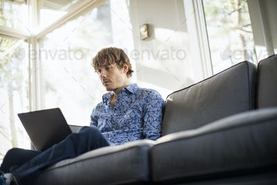 Low angle view of a man sitting on a sofa looking at his laptop.