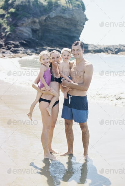A couple with their sun and daughter, a family on the beach looking at the camera, smiling.