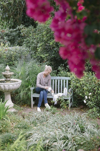Woman sitting on a wooden bench in a garden, taking a break.