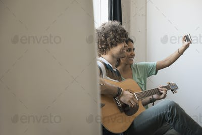 Loft living. A young man playing guitar and a woman beside him taking a selfy with a smart phone.
