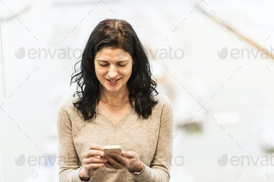 A business woman seated by a window using her smart phone.