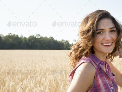 Young woman standing in a cornfield, smiling at the camera.