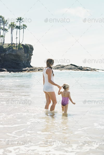 Woman playing with her daughter on the beach.