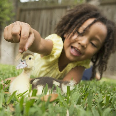 A young girl lying on the grass stroking the head of a duckling.