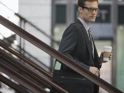 A working day. Businessman in a work suit and tie walking down steps holding a cup of coffee.