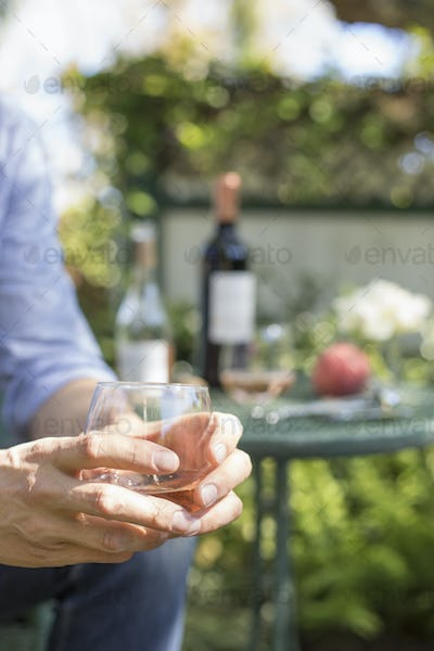 Close up of a man holding a glass of rose wine.