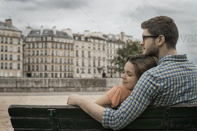 A couple, man and woman sitting close together on a bench by the River Seine.
