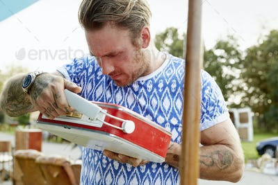 A man in a blue shirt with tatooed forearms, looking at a red vintage radio at a flea market.