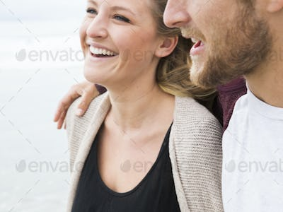 Close up of a smiling young man and young woman on a beach.