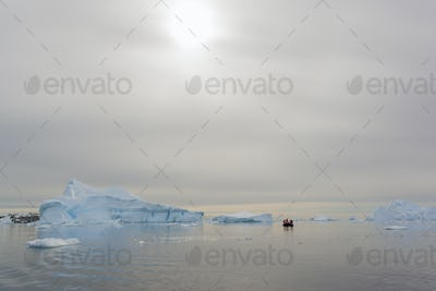 View of a group of people in a rubber boat near and iceberg in the Antarctic.