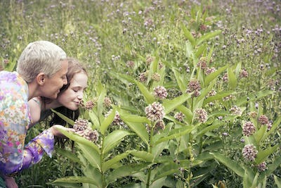 A mature woman and a young girl in a wildflower meadow looking closely at the flowers.
