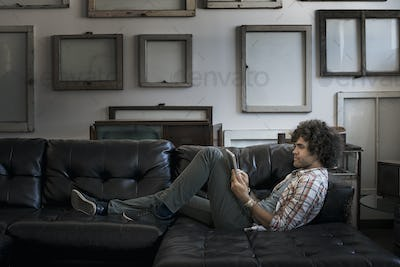 Loft decor. A wall hung with blank canvases. A man on a sofa using a digital tablet.