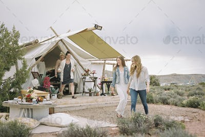 Group of friends enjoying an outdoor meal, a tent in the background.