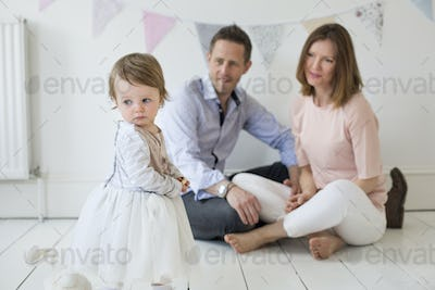 Couple with their young daughter sitting on the floor in photographers studio, posing for a picture.