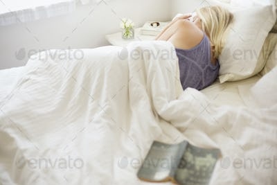 Blonde woman sleeping in a bed with white linen.