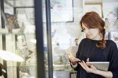 A mature woman holding a digital tablet, stock-taking in a small shop.