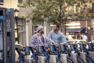 Two men by a rack of bicycles for hire in a city park