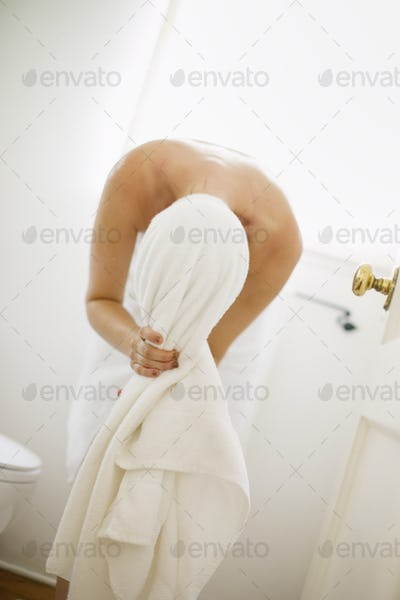 Woman wrapped in a white towel standing in a bathroom, wrapping her hair in a towel.