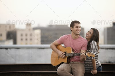 A man playing a guitar to a woman, on a rooftop terrace overlooking a city at dusk.