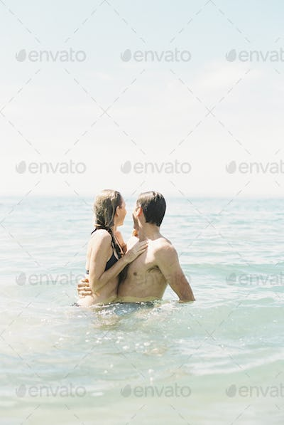 Couple hugging each other, in waist deep water.