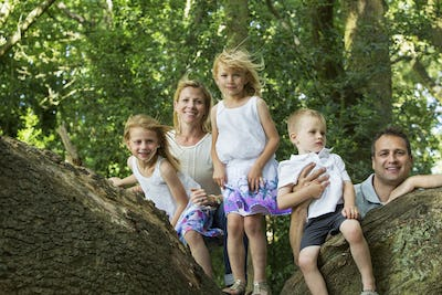 Family with three children by a tree in a forest, posing for a picture.