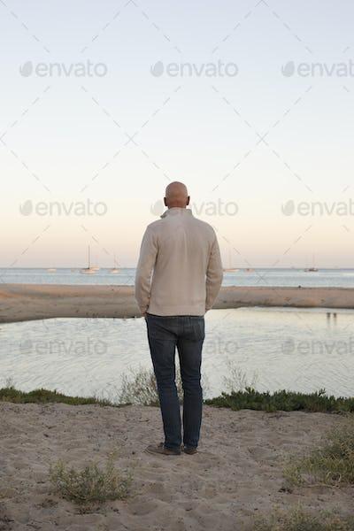 Bald man standing on a sandy beach by the ocean.