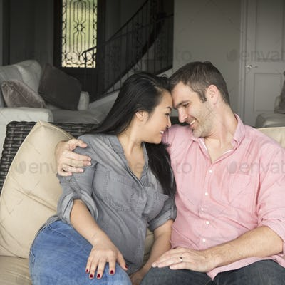Smiling man and woman sitting on a sofa, hugging, and looking at each other.