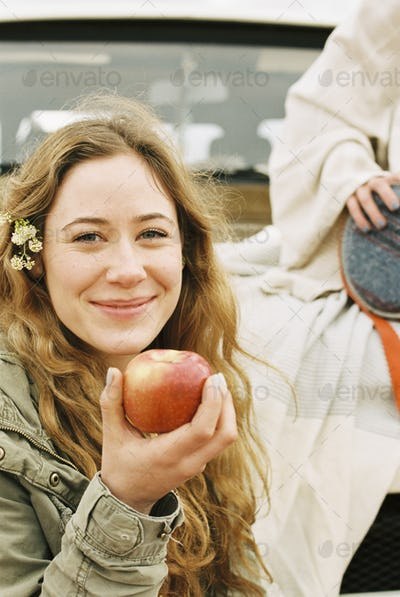 A young woman holding out a red skinned apple.