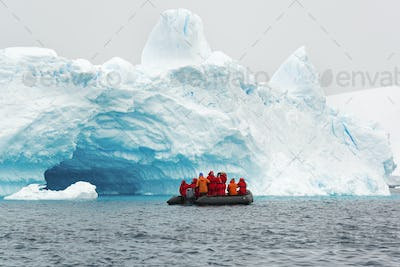 Group of people crossing the ocean in the Antarctic in a rubber boat, icebergs in the background.