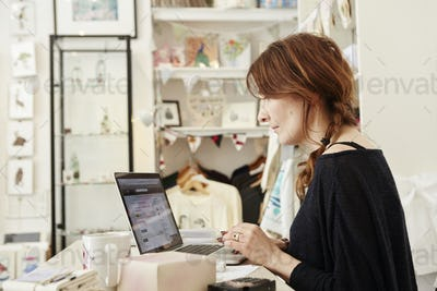 A woman in a small crafts supplier and gift shop, using a laptop, working,