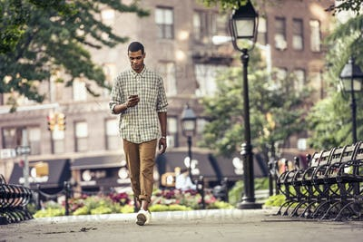 A man walking through a town square looking at his smart phone