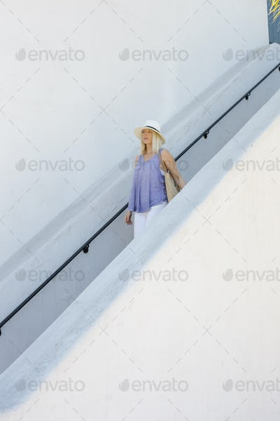 Blond woman wearing a hat walking down a staircase.