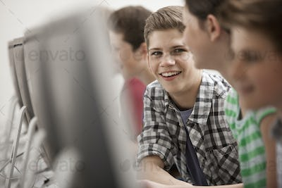 A group of young people, boys and girls, working at computer screens in class.