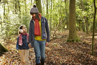 An adult woman and a young girl walking through the beech woods in autumn.