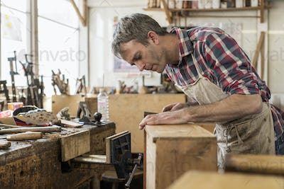 An antique furniture restorer in his workshop using a hand tool to smooth a wooden object.