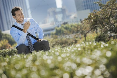 A young man on a park bench in the city, using a cell phone.