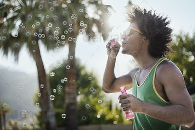 A young man blowing bubbles using a bubble wand.