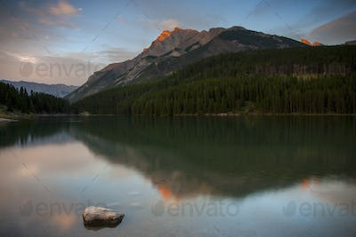 View across a lake towards the mountains in the Canadian Rockies at sunset.