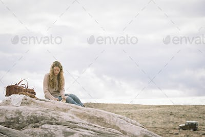 Woman sitting on a rock, a leather bag beside her.