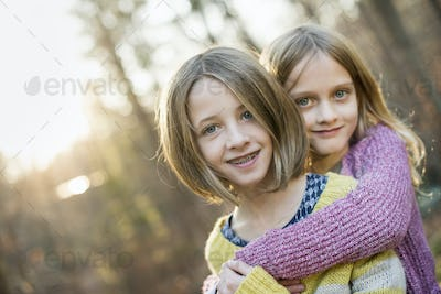 Two smiling girls in a forest, hugging each other.
