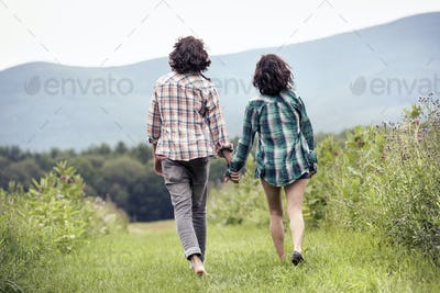 A couple, man and woman walking through a meadow hand in hand, rear view.