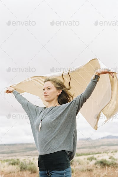 Woman standing in open space with her arms raised, holding a wrap which is fluttering in the wind.