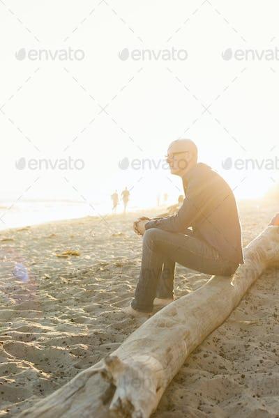 Bald man sitting on a log on a sandy beach.