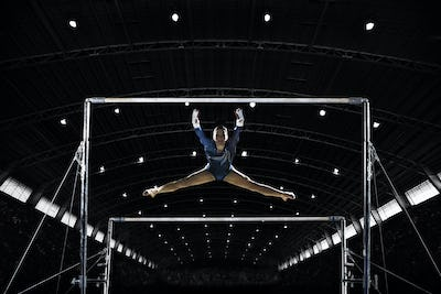 A female gymnast, a young woman performing on the parallel bars performing, with legs extended.