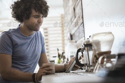 Loft living. A young man sitting with a cup of coffee, holding a digital tablet.