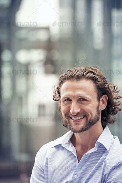 A man with curly hair and a beard on a city street.