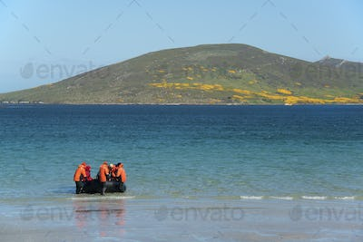 A group of people in a rubber boat landing on a beach on the Falkland Islands.