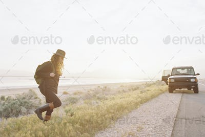 A woman wearing a hat and carrying a backpack near a 4x4 car,