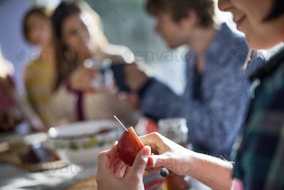 A group of people sitting at a table, eating and chatting. A woman slicing an apple.